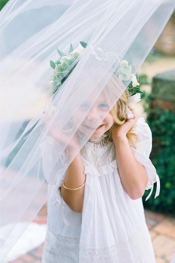 flower girl peaking through veil
