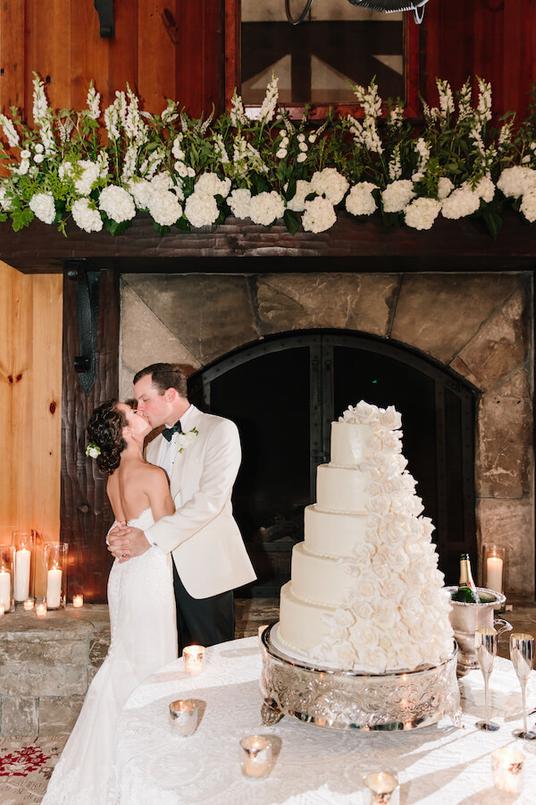 bride and groom kiss by cake
